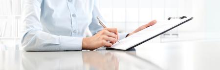 De handen die van de vrouw op blad in een klembord met een pen schrijven, die op bureau wordt geïsoleerd. Stockfoto