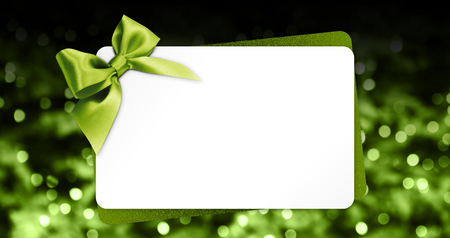 greeting gift card with green ribbon bow isolated on blurred christmas lights background and white template copy space.