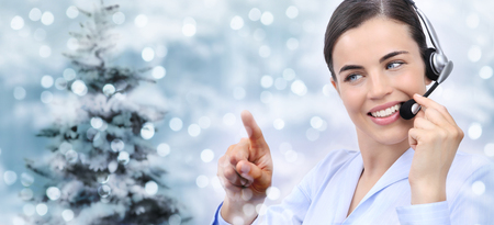 christmas theme smiling woman with headset touch screen on christmas lights background.