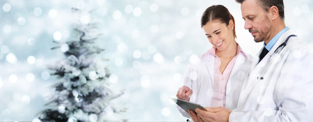 christmas doctors with digital tablet on blurred lights with tree.