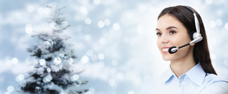 christmas theme woman with headset smiling isolated on christmas background. Stock Photo