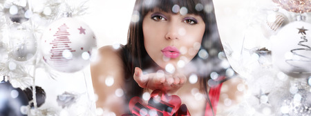 christmas woman blowing glitter on christmas background with balls and blurred lights.