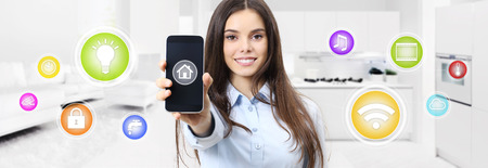 smart home smiling woman showing cell phone screen with colored symbols on kitchen and living blurred background .