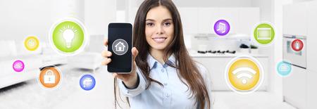 mulher sorridente inteligente mostrando a tela do celular com símbolos coloridos na cozinha e vivendo fundo desfocado. Foto de archivo