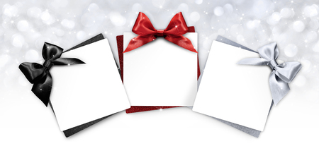 gift cards with black, red and silver ribbon bow Isolated on christmas bright lights background. Stock Photo