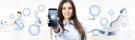 dental care smiling woman showing smart phone, teeth icons and symbols on dental clinic with dentist's chair background web banner template. Standard-Bild