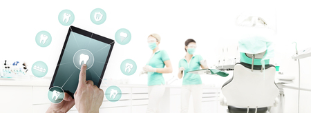 dentist hand touch digital tablet screen teeth icons and symbols on dental clinic with dentist's chair background web banner template contact us concept. Stockfoto