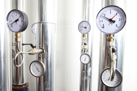 manometer, pipes and faucet valves of heating system in a boiler room. Stock Photo