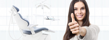 dental care concept, beautiful smiling woman hands thumbs up on dentist clinic with chair background, web banner template. Stok Fotoğraf