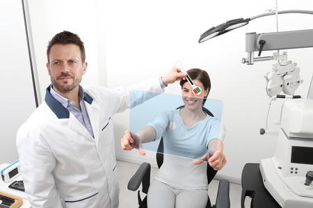 optometrist examining eyesight, woman patient pointing at the hole on plexiglass, ocular dominance test.