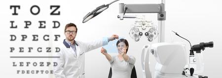 眼科医は、眼科医のオフィスのプレキシガラスの穴に視力の女性患者を指し示すチャートを調べる, 眼支配テスト. 写真素材 - 93874617