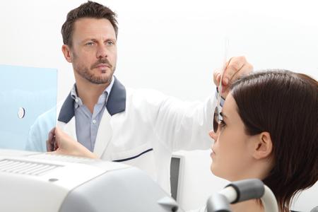 optometrist examining eyesight, woman patient pointing at the hole on plexiglass, isolated on white, ocular dominance test.