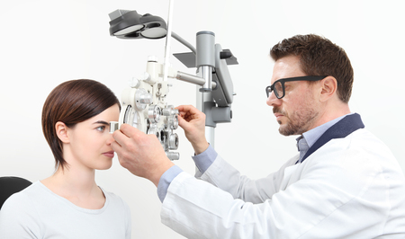optometrist doing eyesight with woman patient measurement with optical phoropter isolated on white. Stock Photo