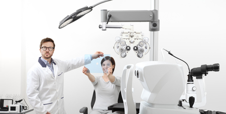 optometrist examining eyesight woman patient pointing at the hole on plexiglass in optician office, ocular dominance test.