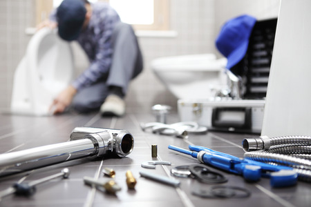 plumber at work in a bathroom, plumbing repair service, assemble and install concept. Stock Photo