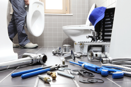 plumber at work in a bathroom, plumbing repair service, assemble and install concept. 版權商用圖片