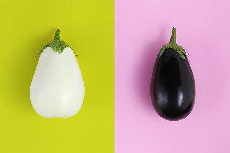 white and black eggplants isolated on green and pink background. Banco de Imagens