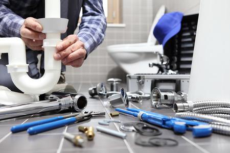 fontanero en el trabajo en un baño, servicio de reparación de fontanería, ensamblar e instalar el concepto. Foto de archivo