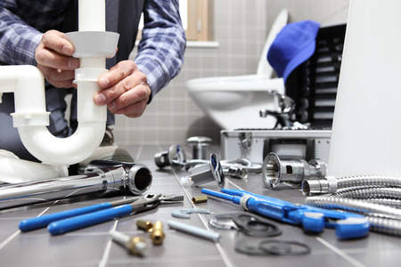plumber at work in a bathroom, plumbing repair service, assemble and install concept. Stockfoto