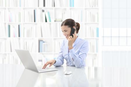Mujer sonriente de negocios o un empleado que trabaja en su escritorio de oficina con la computadora y habla por teléfono, contáctenos y apoye el concepto.