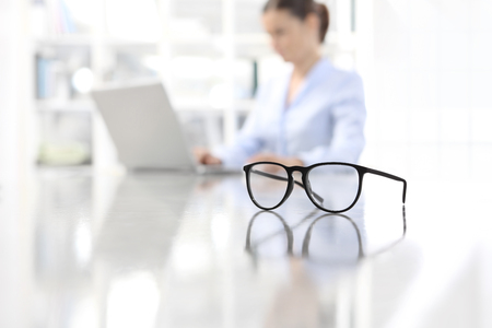 eyeglasses leaning on desk and woman working on computer at office in background.