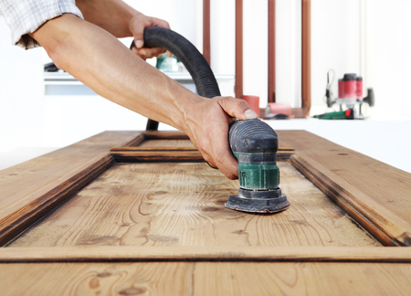 carpenter work the wood with the sander. Banque d'images