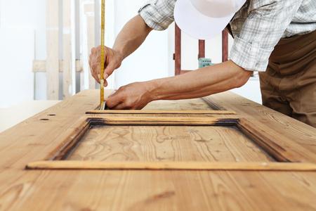 A carpenter work the wood, vintage wooden door.