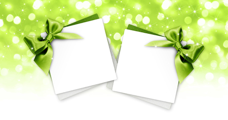 gift cards with green ribbon isolated on white blurred lights christmas background. Archivio Fotografico