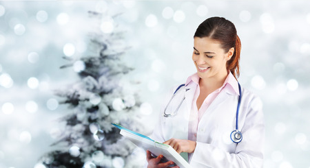 christmas smiling doctor with folder on blurred lights with tree. Stock Photo