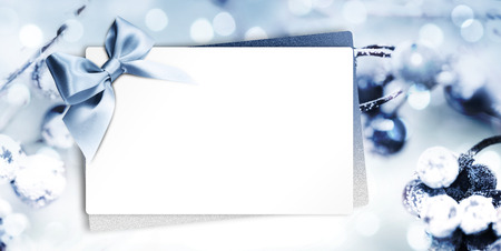gift card or greeting card with blue ribbon on blurred blue christmas background, white copy space.