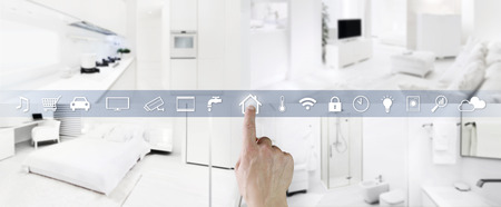 smart home control concept hand touch screen icons with interiors, living room, kitchen, bedroom and bathroom on blurred background.