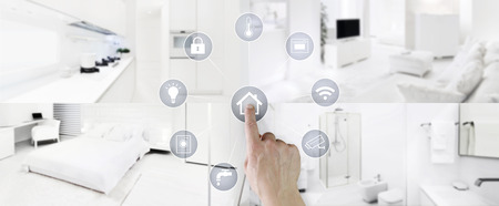 smart home control concept hand touch screen icons with interiors, living room, kitchen, bedroom and bathroom on blurred background. Reklamní fotografie - 115775964