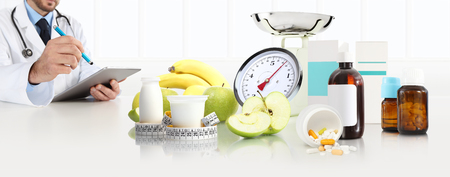 dietitian nutritionist doctor prescribes at the desk with apple, yogurt, medical drugs, tape meter and scales, healthy and balanced diet concept, web banner and copy space template.