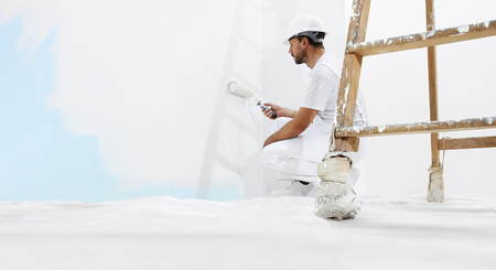 painter man at work, with wooden ladder and blank wall. Stockfoto