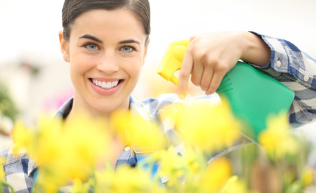 smiling woman spraying flowers at garden, spring concept.