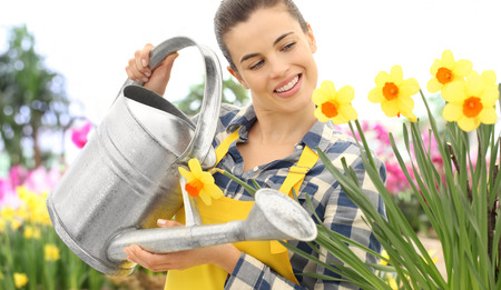 smiling woman watering flowers at watering can spring flowering concept. Stok Fotoğraf