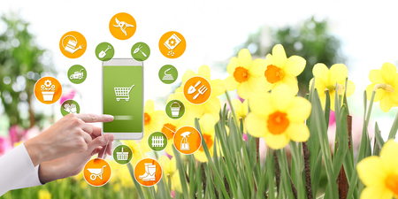 gardening equipment e-commerce concept, online shopping on smart phone, hand pointing and touch screen with tools icons, spring flower plants background.