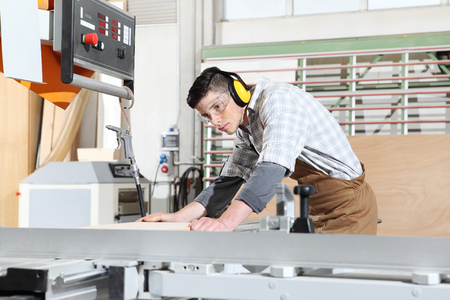 carpenter working in the joinery, cutting a wooden board, protected with ear muffs and glasses, Stockfoto