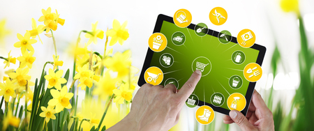gardening equipment e-commerce concept, online shopping on digital tablet, hand pointing and touch screen with tools icons, on spring flower plants background Stok Fotoğraf