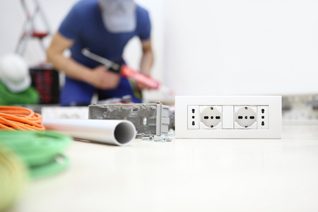 electrician at work with silicon gun in hand, install socket, electric circuits, electrical wiring,