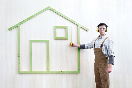 house construction renovation concept handyman carpenter worker man with measure and show model of a wooden house, custom solutions,
