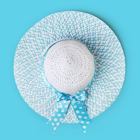 top view summer beach round straw hat with spotted bow ribbon isolated on light blue background.