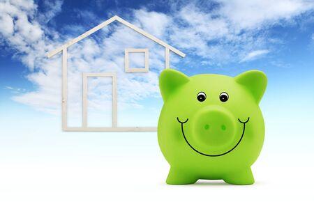salvadanaio con forma di casa in legno isolato su sfondo blu cielo, edificio verde e concetto di risparmio energetico.