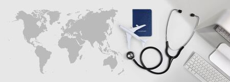 international medical travel insurance concept, stethoscope, passport, computer and airplane on desk office banner with global map.