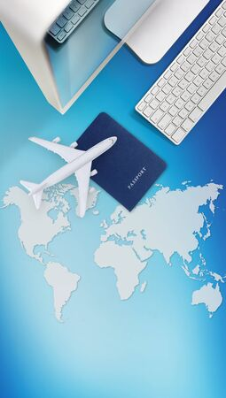 air travel concept, computer, passport and airplane isolated on blue background with global map. Stockfoto