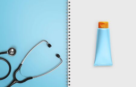 medical sunscreen, notebook paper pages with blue stethoscope isolated on white background, copy space blank template. 版權商用圖片