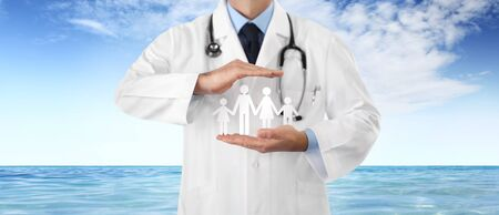 holiday medical insurance concept, doctors hands protect a family icon with the sea and blue sky in the background, copy space and web banner template. Stockfoto