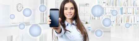 Smiling woman shows smartphone with empty icons isolated on interior office background. Stockfoto