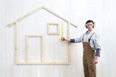 house construction renovation concept handyman carpenter worker man with measure and measure