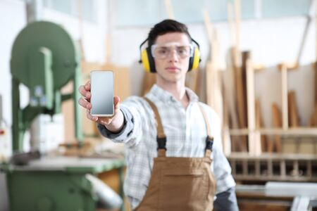 carpenter man show the mobile phone isolated on carpentry background.